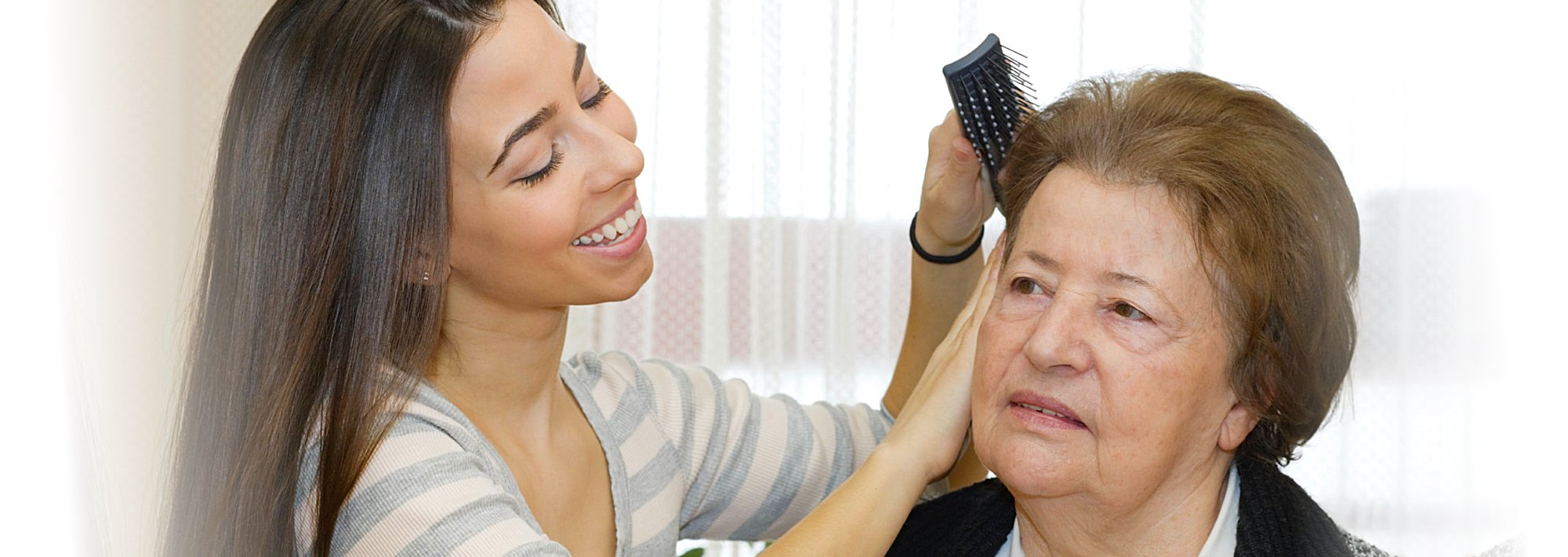 Caregiver combing the hair of a senior